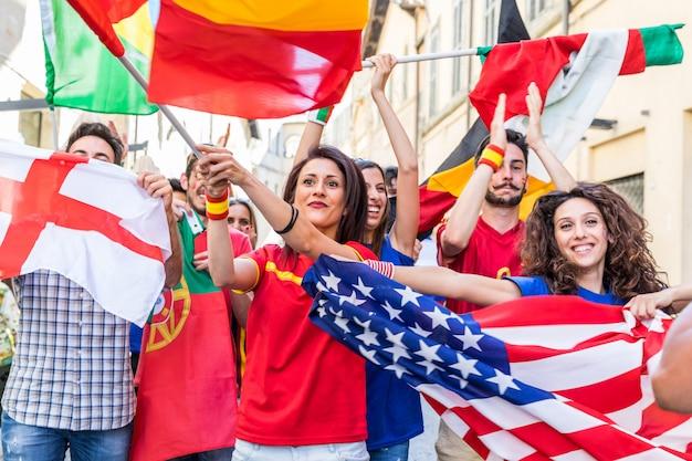 Felices fanáticos simpatizantes de diferentes países caminando y cantando juntos.