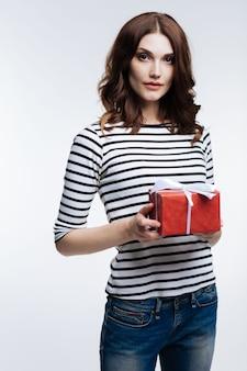 Felices fiestas. encantadora mujer joven de pelo castaño en un jersey de rayas sosteniendo una caja de regalo roja atada con un lazo mientras posa sobre fondo gris