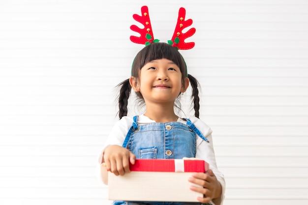 Felices fiestas y navidad niña linda alegre celebración actual caja de regalo en la sala blanca.