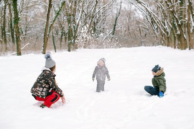 Felices fiestas navideñas. encantadora familia jugando con nieve en invierno caminar al aire libre.