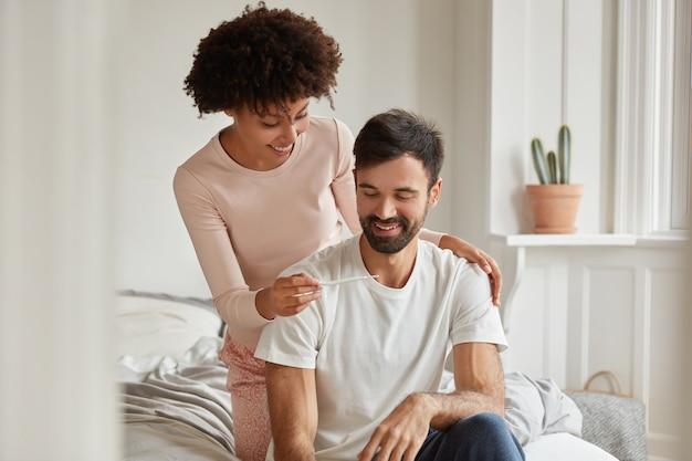 Felices futuros padres de raza mixta miran positivamente la prueba de embarazo, se regocijan con las buenas noticias en la mañana