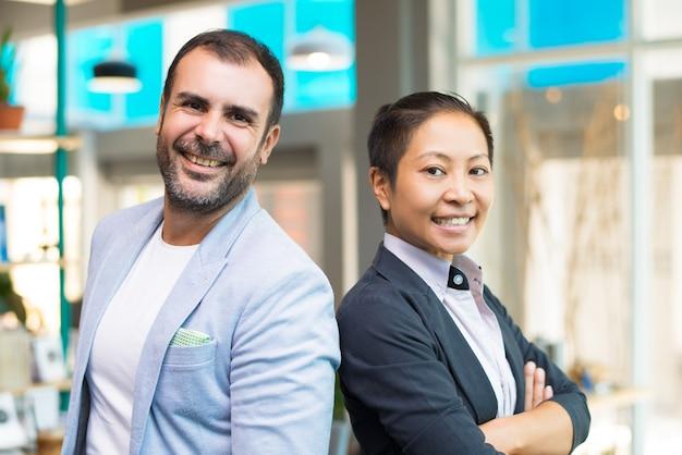 Felices gerentes asiáticos y latinos sonrientes y parados uno al lado del otro