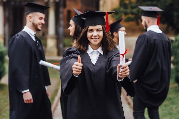 Felices graduados maestros graduados de pie en una fila y levanta el dedo