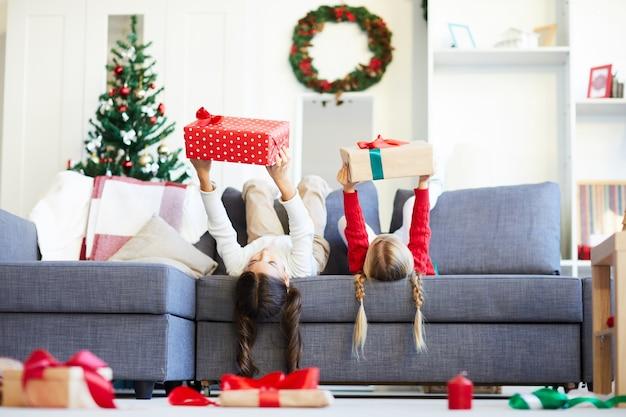 Felices hermanas niñas desenvolver regalos de navidad