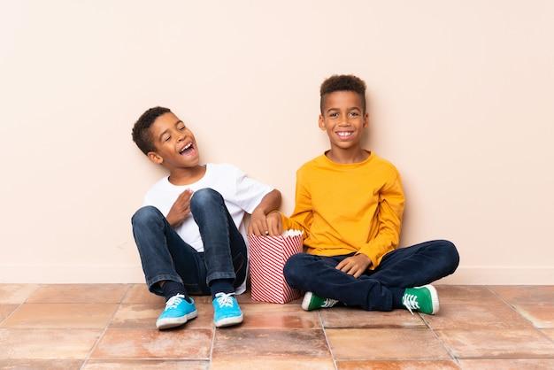 Felices hermanos afroamericanos con palomitas de maíz