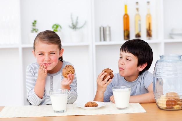Felices hermanos comiendo galletas y bebiendo leche