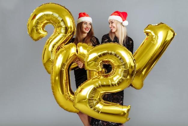 Felices hermosas mujeres jóvenes en elegantes vestidos de fiesta negros sexy con globos de oro 2021
