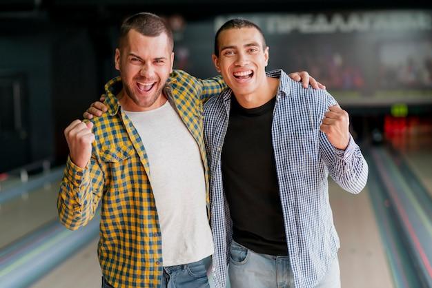 Felices hombres jóvenes en el club de bolos
