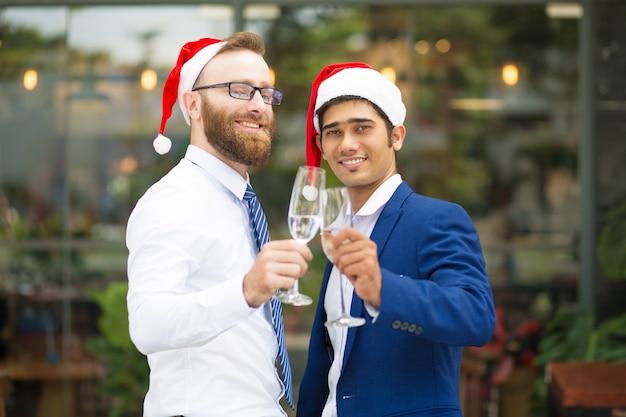 Felices hombres multiétnicos emocionados tintineando flautas de champán
