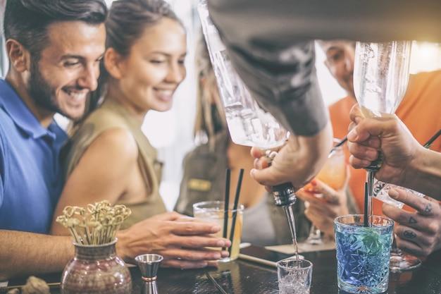 Felices jóvenes amigos divirtiéndose disfrutando de bebidas en el bar mientras barman preparando cócteles y tiro