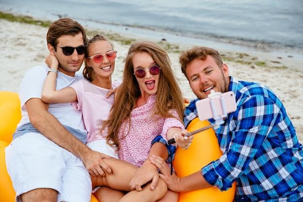 Felices jóvenes amigos en gafas de sol, descansando juntos, tomando un selfie en teléfono móvil