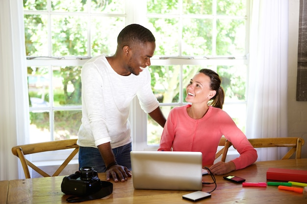 Felices jóvenes amigos con laptop y cámara de fotos en la mesa