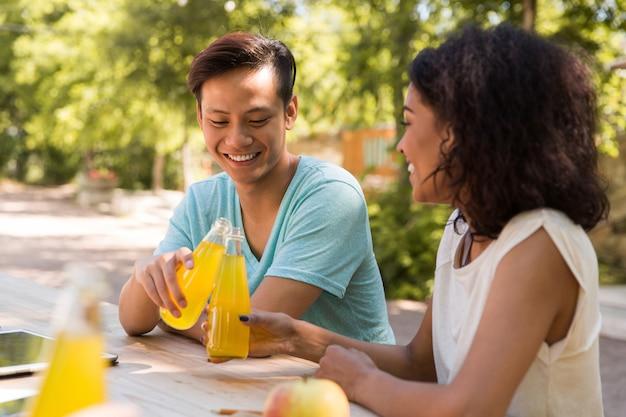 Felices jóvenes amigos multiétnicos estudiantes afuera bebiendo jugo