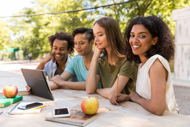 Felices jóvenes amigos multiétnicos estudiantes al aire libre usando tableta