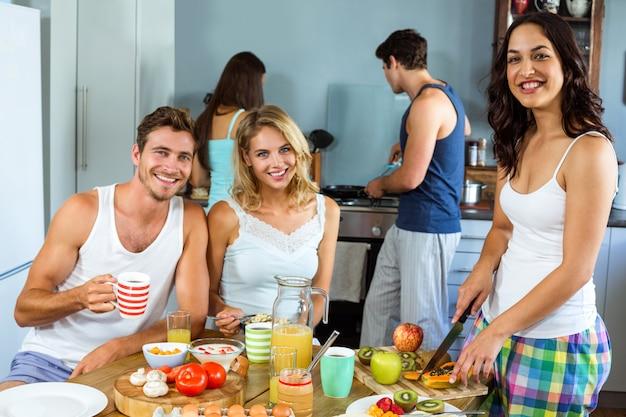 Felices jóvenes amigos preparando el desayuno en la cocina