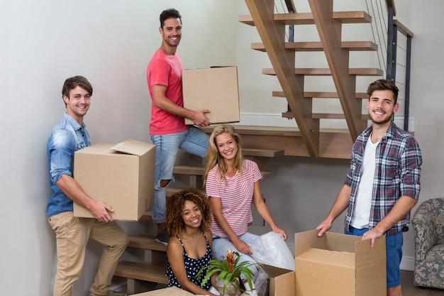 Felices jóvenes amigos que se mudan a una casa nueva