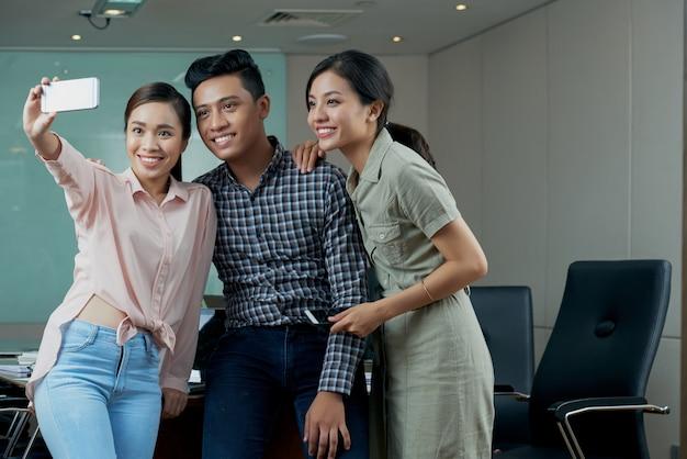 Felices jóvenes colegas asiáticos en ropa casual tomando selfie en oficina