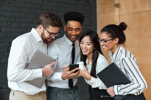 Felices jóvenes colegas de negocios mediante teléfono móvil.