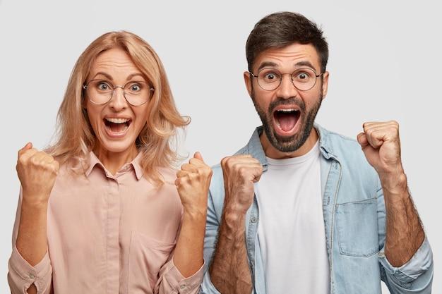 Felices los jóvenes colegas o socios comerciales se regocijan con el éxito, aprietan los puños y exclaman con triunfo