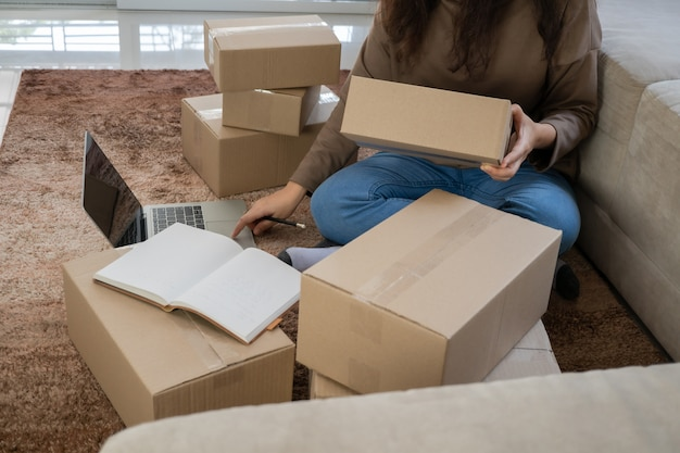 Felices jóvenes empresarios asiáticos están organizando cajas para entregar productos a los clientes.