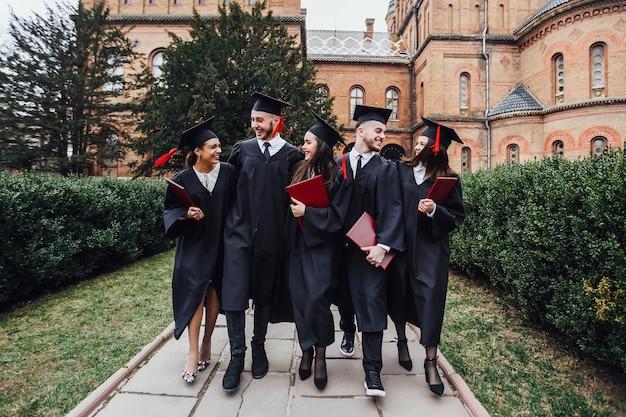 Felices jóvenes graduados en capas con diplomas caminando en la universidad jardín.