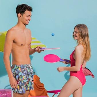 Felices jóvenes novios en ropa de playa jugando ping pong en estudio