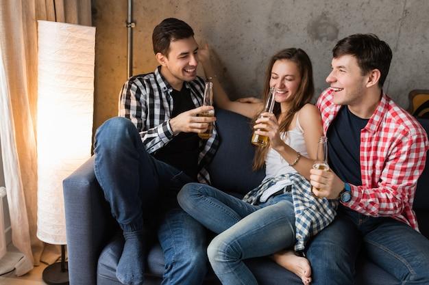 Felices los jóvenes sentados en el sofá, bebiendo cerveza, cerca de las manos brindando, divirtiéndose, fiesta en casa de amigos, compañía hipster juntos, dos hombres una mujer, sonriendo, positivo, relajado, pasar el rato, riendo