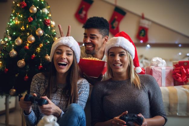 Felices juguetones amigos de navidad con sombreros de santa y suéteres disfrutando de casa para las vacaciones.
