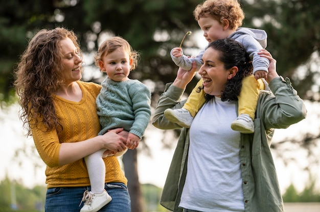 Felices madres lgbt afuera en el parque con sus hijos.