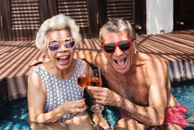 Felices mayores bebiendo prosecco en la piscina