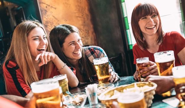 Felices mejores amigos bebiendo cerveza en el bar