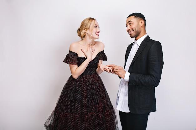 Felices momentos encantadores de linda pareja de chico guapo haciendo propuesta de matrimonio a hermosa joven rubia en vestido de lujo. expresando felicidad, enamorado, día de san valentín.