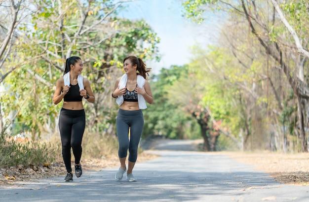 Felices las mujeres asiáticas jóvenes en ropa deportiva para correr y correr al aire libre. concepto de salud de estilo de vida