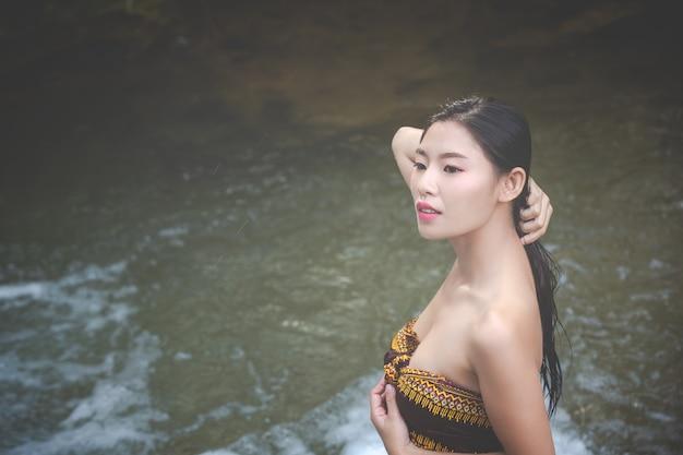 Felices mujeres bañándose en la cascada natural.