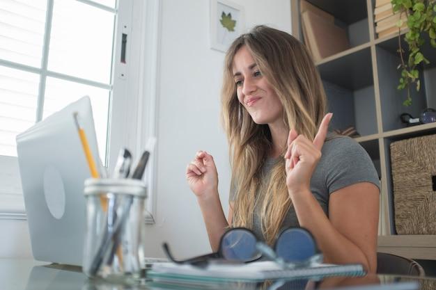 Felices mujeres bastante jóvenes disfrutan de una videoconferencia en línea con una computadora portátil y conexión a internet