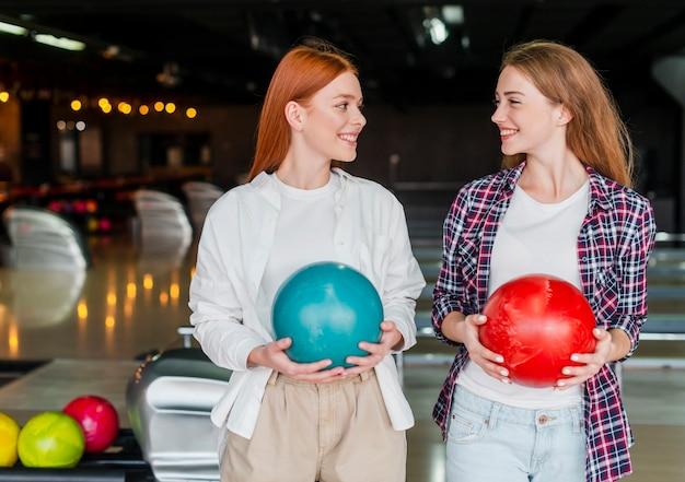 Felices mujeres jóvenes con coloridas bolas de boliche
