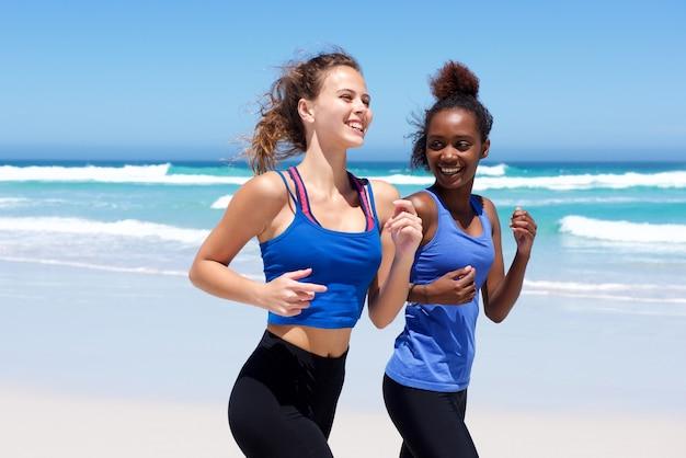 Felices mujeres jóvenes corriendo en la playa
