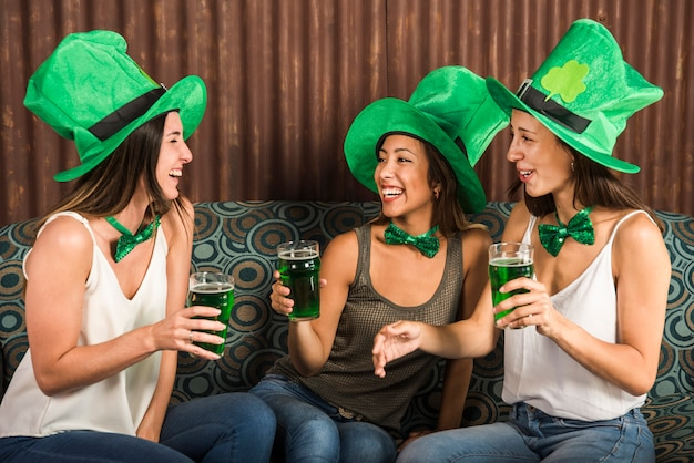 Felices mujeres jóvenes con vasos de bebida en sofá