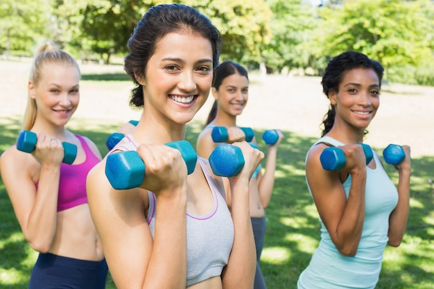 Felices mujeres multiétnicas levantando pesas