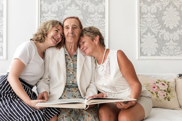 Felices mujeres de tres generaciones sentadas en un sofá con un álbum de fotos.