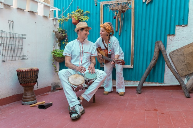 Felices músicos callejeros tocando música y cantando en la calle en la habana vieja