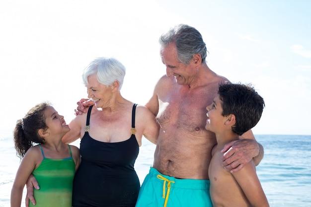 Felices nietos y abuelos de pie en la playa