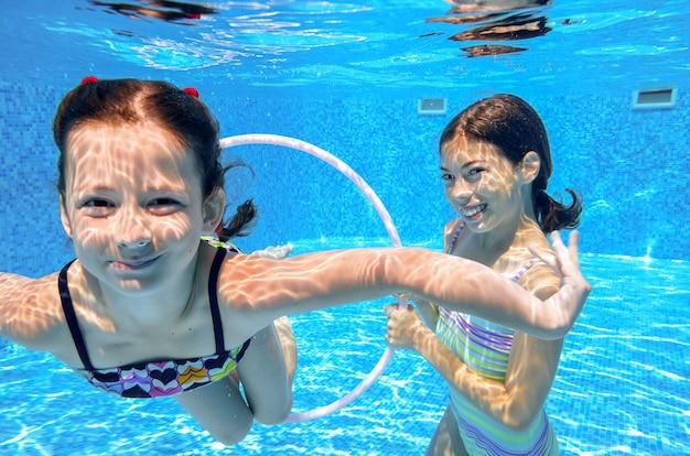 Felices los niños activos juegan bajo el agua en la piscina