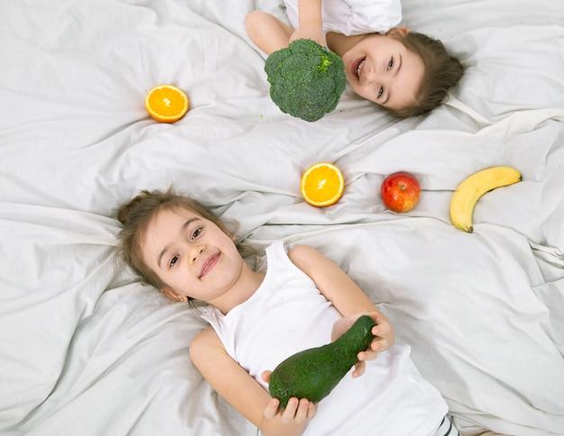 Felices los niños lindos juegan con frutas y verduras. alimentos saludables para niños.