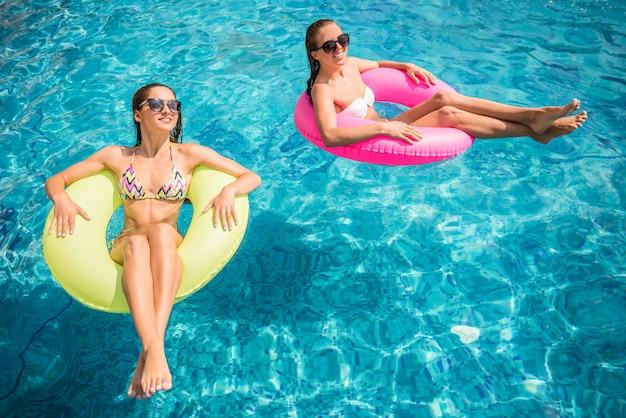 Felices novias se divierten en la piscina.