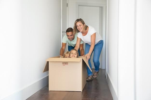 Felices padres caucásicos jugando con niños sentados en caja de cartón en casa nueva