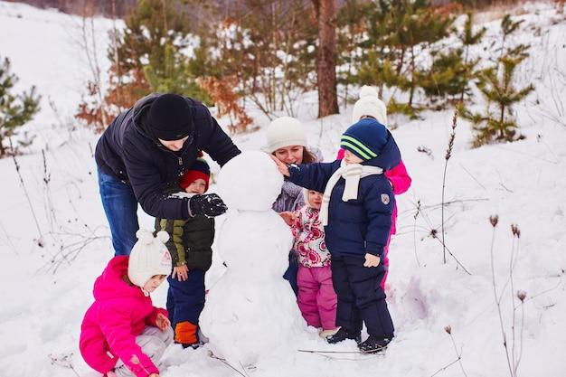 Felices padres e hijos crean un gran muñeco de nieve.