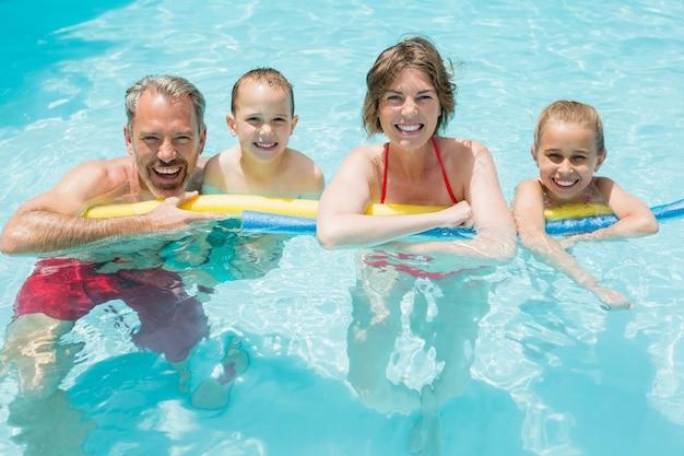 Felices padres e hijos en la piscina