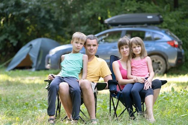Felices los padres de familia jóvenes y sus hijos descansando juntos en el camping en verano.