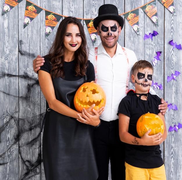 Felices padres con hijo posando para halloween